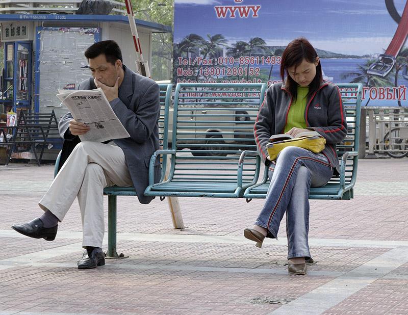 Doi oameni citind pe o banca